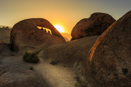 Three people sitting in the mouth of Mobius Arch enjoying the fist warm sunrays of the day