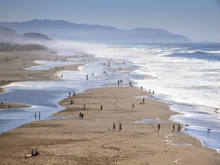 Busy beach full of walking and playing people in San Francisco, California