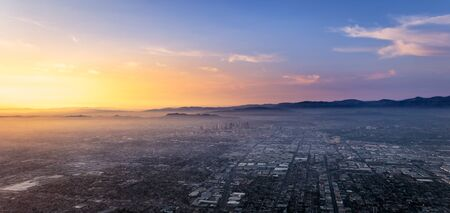 Beautiful sunset over the center of Los Angeles viewed from a rising airplane 免版税图像