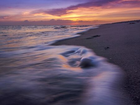 Waves flowing through human footsteps, reflecting the beautiful sunset on a Florida beach