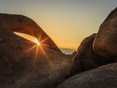 The morning sun shining through the mouth of Mobius Arch in the Alabama Hills, California