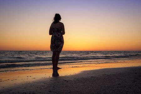 Silhouette of a beautiful woman admiring the sunset on a beach in Florida Stock Photo