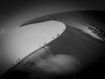 Group of tourists climbing a big dune at sunrise shadows casting in the sand, Namibia