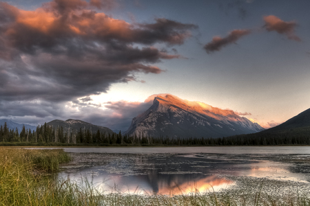 Pink clouds moving over the top of a mountain during a spectacular sunset in Banff National Park, Canada
