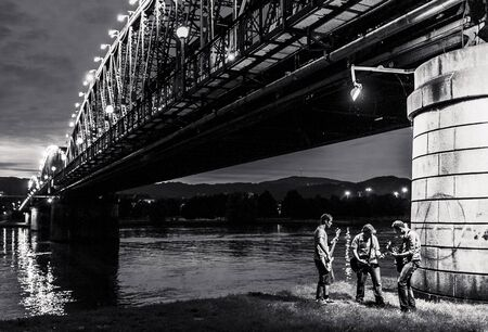 Three musicians rocking under a spotlight of the old Linz railway bridge
