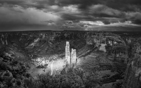 Spectacular spotlight on the spider-rock of Canyon de Chelly National Park during a thunderstorm - black & white 免版税图像