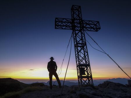 Silhouette of a man on top of a mountain looking into the rising sun