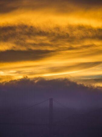 The golden-bridge bridge shines through a cloud during an amazing sunset in San Francisco, California