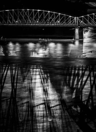 Abstract portrait of the old Linz railroad bridge cast shadows in the dark danube