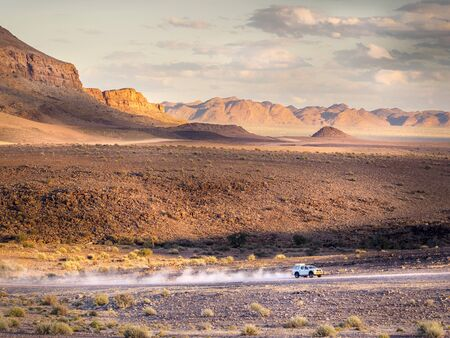 White Pick-Up leaving a trace of dust in the arid mountains of south Namibia