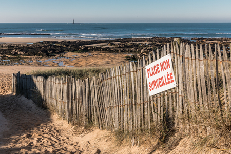 littoral: French sign Unguarded beach on wood fence Stock Photo