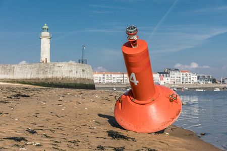 Buoy at the entrance to the harbor of Saint-Gilles Croix de Vie with the tour Josephine on the background (Vendee, France) Stock Photo