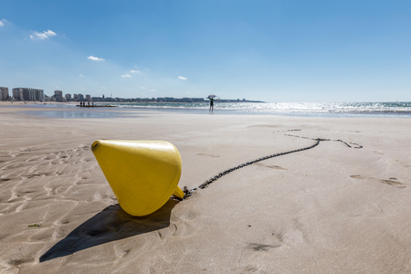 europe: Yellow conical buoy on the beach at low tide