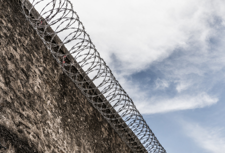 Prison wall with barbed wire Stock Photo