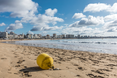 building a chain: Les Sables dOlonne beach at low tide with a yellow buoy (Vendee, France) Stock Photo
