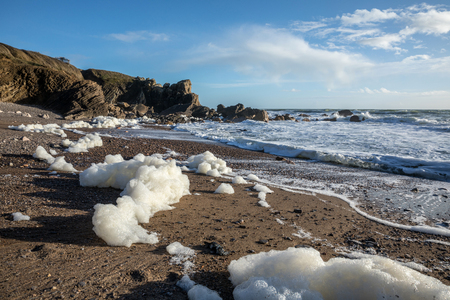 Sea foam created by the agitation of seawater on the beach of Cayola (Les Sables dOlonne, France)