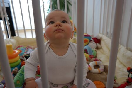 playpen: Baby schaut nach oben in Laufstall Stock Photo