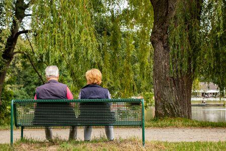 Couple de personnes âgées sur un banc dans un parc au bord d'un lac, tourné par derrière
