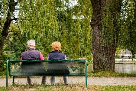 Senior couple on a bench in a park at a lake, shot from behind