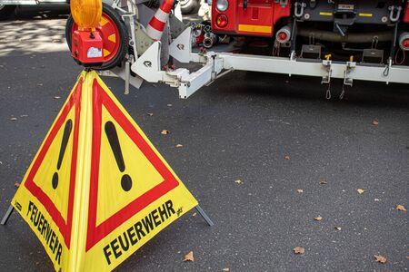 Triagle shows fire brigade at work. German sign, fire brigade truck in background