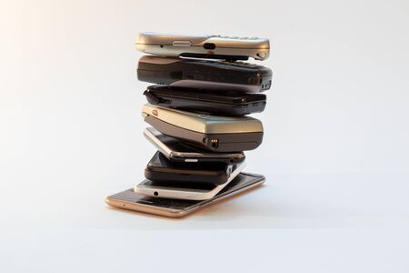 collection of old mobile phones stacked, piled in front of white background Standard-Bild