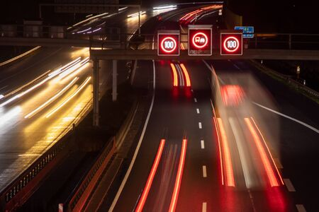 traffic control system with speed display at night, lightstripes of cars