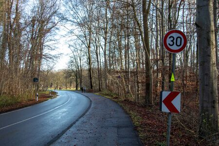 curve of a country road in the forest with speed limit sign, 30 kmh Banco de Imagens