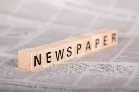 newspaper text on wooden cubes, newspaper as background, perspective view Фото со стока