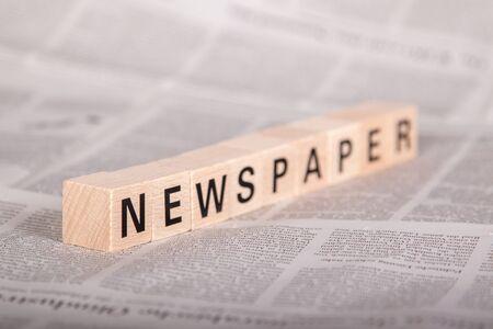 texte de journal sur des cubes en bois, journal en arrière-plan, vue en perspective Banque d'images