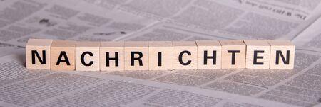 Duitse tekst Nachrichten, wat betekent nieuws, op houten kubussen, krant als achtergrond Stockfoto