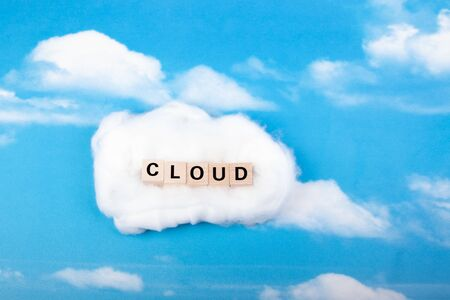 word cloud made of wooden blocks, sky with clouds as background