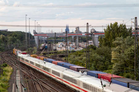 Huerth, NRW, Germany, 06 27 2020, cargo train before skyline of cologne, container station cologne Eifeltor, passenger train