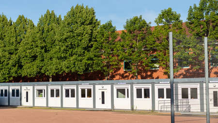 residantial container at a school, set up on a clay court, sunny day