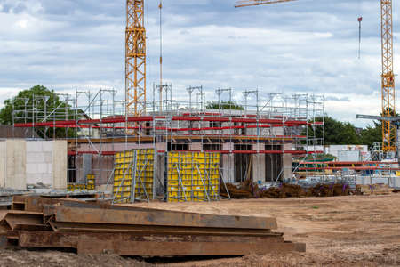 Huerth, NRW, Germany, 06 06 2020, house construcktion side with contruction cranes and scaffolding, cloudy day Editorial