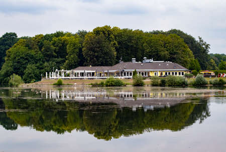 Cologne, NRW, Germany, 06 11 2020, restaurant with terrace at likeside decksteiner weiher, reflection in the lake, cloudy day