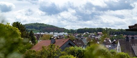 view over a village, rooftops, hills in the background, cloudy sky Stock Photo