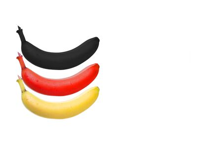 three bananas in yellow, red and black as german flag, white background Stock Photo
