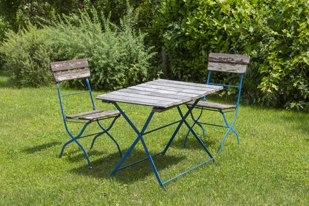 two metal chairs and a table in a garden surrounded by bushes, outdoors