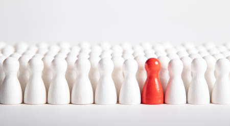 many white wooden figurines and one red Reklamní fotografie