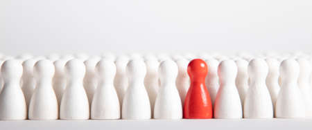 many white wooden figurines and one red