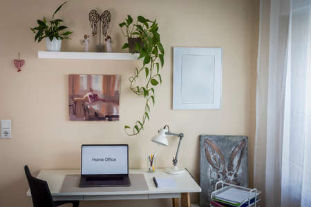 desk with laptop and chair in front, shelves with plants and on the right a window with a white curtain, home office, indoors