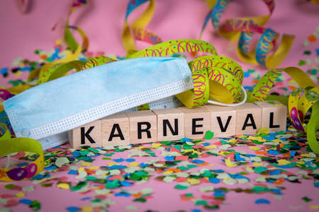 German word KARNIVAL on wooden blocks under a face mask with confetti and streamers, pink background