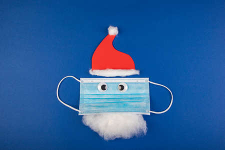 handmade santa clause with moth protection, face mask, red cap and beard, as a symbol for impact in covid virus in Christmas season, blue background