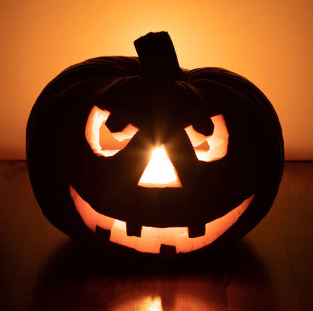 halloween pumpkin with smiling face on fir branches, four teeth. light illuminating the pumpkin from inside, light reflection in the background 免版税图像