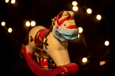 Toy rocking horse wears a face mask as a symbol of the effects of the Covid-19 virus on the 2020 Christmas party, light points on black background Stok Fotoğraf