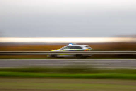 German police car in motion on a highway behind guard rails, outdoors, alarm lights on