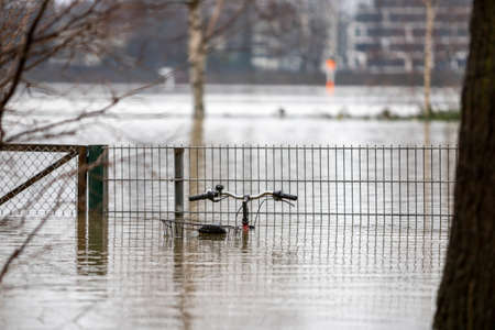 bike and fence nearly completely covered by high water of rhine river in Cologne, bokeh background