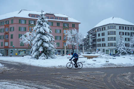 Zurich, Switzerland - January 15th 2021: A cyclist crossing a snowy square