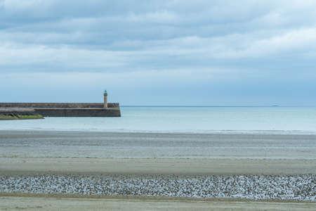 Beautiful beach at the Brittany Atlantic coast, France, with wave-breaker. 免版税图像