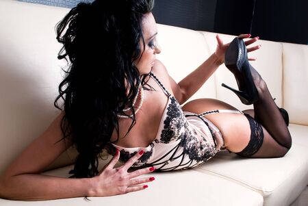 Attractive female in lingerie sitting on a couch Stock Photo - 8063920